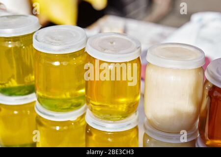 Diferentes variedades de miel blanca y dorada dulce en el mercado de los agricultores. Miel natural en varios tarros