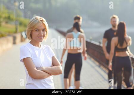 Chica deportiva sonrisas en el fondo de amigos atletas en el parque