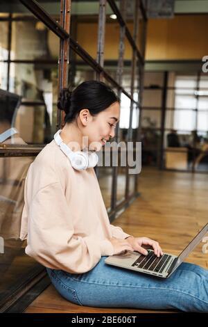Imagen de una joven hermosa mujer asiática trabajando en el ordenador portátil mientras se sentaba en el suelo de la oficina