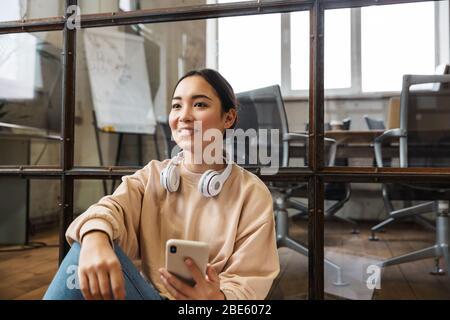 Imagen de una joven hermosa mujer asiática sonriendo y sosteniendo el teléfono celular mientras trabajaba en la oficina