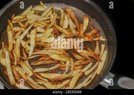 Freír patatas fritas en aceite de oliva caliente en la cocina de la casa. Vista superior de la preparación de patatas fritas caseras recién cortadas en una sartén con aceite hirviendo.