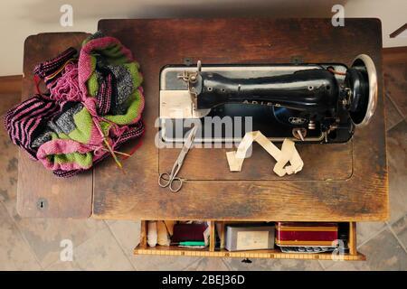 Vista superior de mesa de artesanía con máquina de coser vintage, tejidos y accesorios