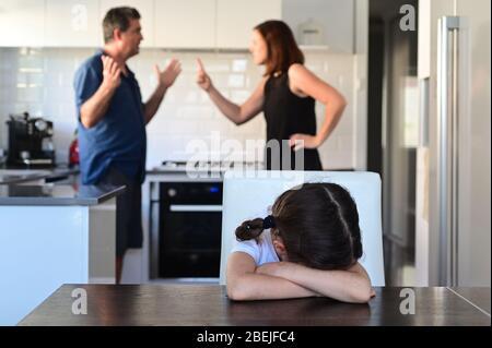 Triste niña sentada en la mesa del comedor cubriendo su cara mientras los padres discutiendo en la cocina de casa en el fondo.