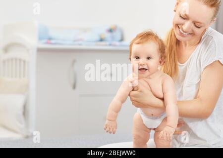 Madre que se acerca a su bebé acostado en una cama