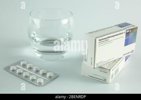 AMSTERDAM, PAÍSES BAJOS - 08 DE ABRIL de 2020: Una caja y tabletas de hidroxicloroquina, también conocida como Plaquenil, con fondo blanco