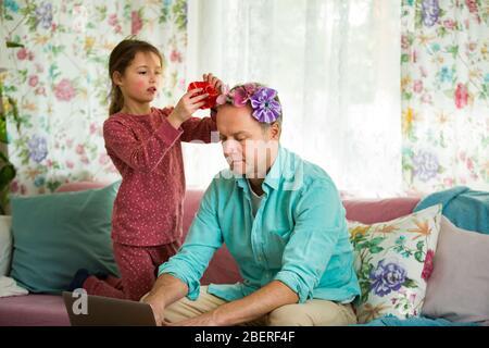 Niño jugando y perturbando a padre trabajando a distancia de casa. Niña peinando el pelo del papá y haciendo peinado. Hombre en el sofá con ordenador portátil