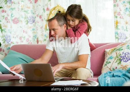 Niño jugando y perturbando a padre trabajando a distancia de casa. Hombre sentado en el sofá con ordenador portátil. Familia pasando tiempo juntos en el interior.