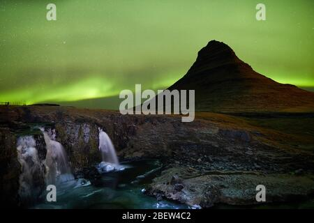 Kirkjufellsfoss, Islandia - 27 de noviembre de 2019: Larga exposición durante la puesta de sol sobre la cascada Kirkjufellsfoss con la montaña Kirkjufell al fondo Foto de stock