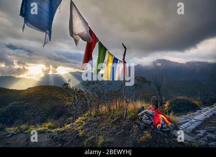Pequeños montones de piedras y banderas de oración tibetano Lung Ta en el Mardi Himal Campamento Base al atardecer nublado picos de las montañas del Himalaya en Nepal