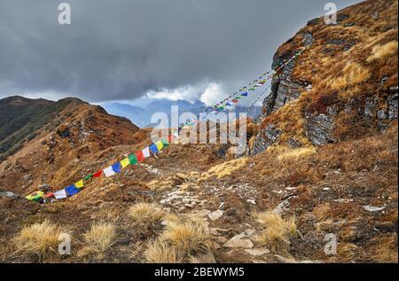 Pequeños montones de piedras y banderas de oración tibetano Lung Ta en el Mardi Himal Campamento Base a nublado picos de las montañas del Himalaya en Nepal
