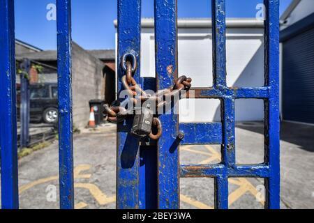 NOTA: IMAGEN 8 DE UN CONJUNTO DE 35 IMÁGENES CON PUERTAS CERRADAS DE NEGOCIOS Y LUGARES QUE ESTÁN CERRADOS DURANTE EL CIERRE del Reino Unido UNA cadena oxidada y candado asegurar puertas de acero pintado de color azul para impedir el acceso a un negocio en una propiedad comercial en Bristol como el Reino Unido sigue en cierre ayudar a frenar la propagación del coronavirus.