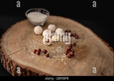 Chocolate blanco dulce casero, coco y avellanas en una rebanada de troncos. Trufas de caramelo bola de nieve