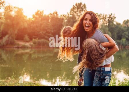 Día de la madre. Familia jugando y divertirse en el lago de primavera. Madre sosteniendo y girando alrededor de las hijas al aire libre.