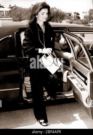 La ex primera Dama DE los Estados Unidos JACQUELINE KENNEDY ONASSIS está a unos pasos de un coche.