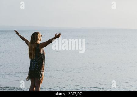 Mujer joven disfrutando de la puesta de sol junto al mar