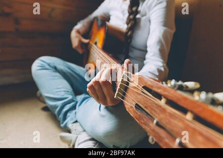 Estancia en casa estancia segura. Mujer joven sentada en casa y tocando la guitarra, con las manos de cerca. Niña adolescente aprendiendo a tocar canciones y escribiendo música. Estilo de vida Hobby Relax Instrument concepto de educación de ocio
