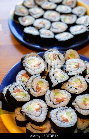 Dos platos redondos de sushi maki casero con salmón, arroz y aguacate sobre mesa de madera