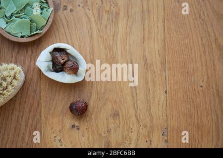 Plano sobre la cabeza de un jabón de barra Alepo y accesorios para la ropa como las bayas de baño sobre un fondo de madera. Concepto de higiene y dermatología,