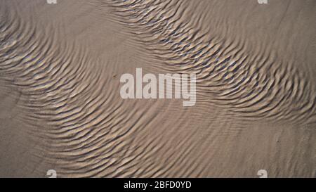Una vista cercana de las ondulaciones en la superficie del agua creadas por el fuerte viento en la arena de una playa Foto de stock