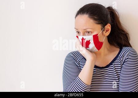 Una niña en un suéter a rayas y máscara médica pintada como la bandera de Canadá, cuidadosamente props su cabeza con su mano y mira hacia el espacio de copia Foto de stock
