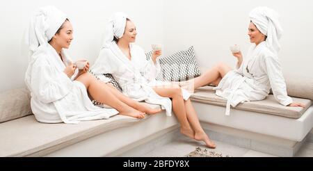 Día de té en el spa. Tres hermosas mujeres se relajan en el spa, beben té y se divierten hablando. Están vestidas con batas de baño, una toalla alrededor de sus cabezas.