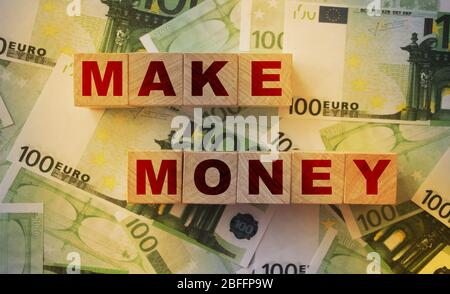 Haga palabras del dinero en los bloques de madera puso en las cuentas de 100 euros. Hacer el concepto de negocio acertado del beneficio