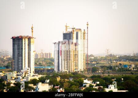 Tiro aéreo de edificio en construcción con múltiples pisos y grúa en la parte superior que se encuentra en el campo. Muestra el rápido desarrollo de Foto de stock