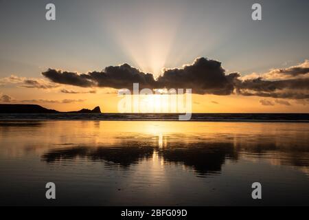Puesta de sol en la playa de la bahía de Rhossili con reflejos de nubes y rayos de sol detrás de las nubes mirando hacia Worm's Head en el Gower, Gales del Sur. REINO UNIDO