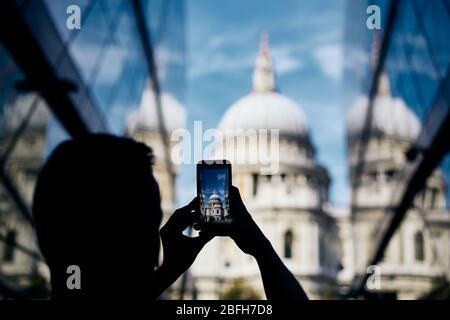 Hombre fotografiando con un teléfono inteligente. Turista tomando una foto de la Catedral de San Pablo en Londres, Reino Unido.