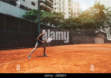 Una joven afroamericana delgada juega al tenis al aire libre en la pista de entrenamiento; hermosa biracial deportes chica en la posición deportiva listo para desviar diez