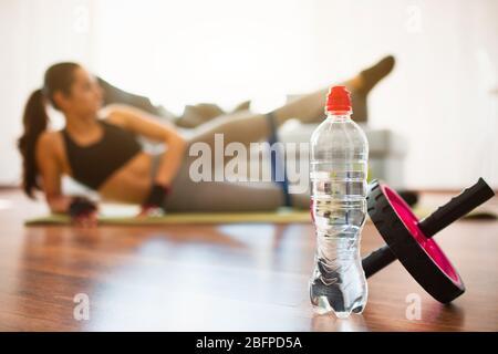 Mujer joven haciendo ejercicio deportivo en la habitación durante la cuarentena. Botella de agua y rodillo de ejercicios abdominales en frente. Estiramientos y entrenamiento de la niña con