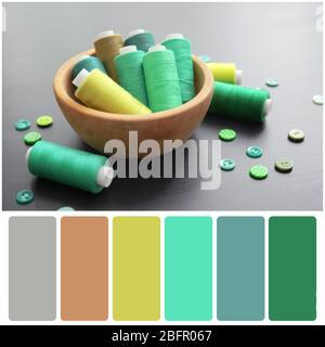Paleta de colores y cuenco con hilos verdes y botones sobre fondo de madera