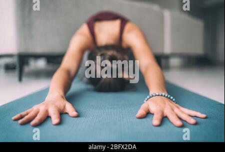 Yoga hogar estirando meditación mujer haciendo niños pose calentamiento estiramiento en el hogar de la sala de estar. Manos tocando la alfombrilla de ejercicios del suelo y la pulsera de mala. Fitness relajación concepto sin estrés. Foto de stock