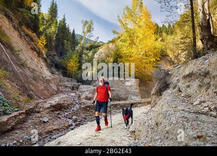 Hombre viejo con barba blanca y negro perro caminando en canyon en época otoñal. Concepto de viaje en el exterior