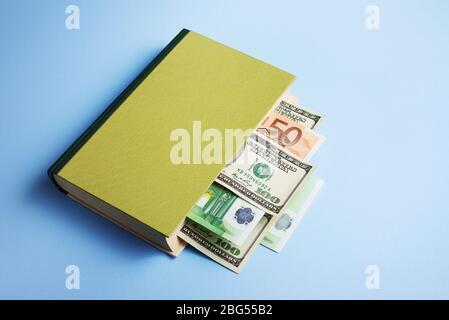 Concepto de alfabetización financiera y gestión del dinero. Libro con un marcador en forma de billete de dólar y euro