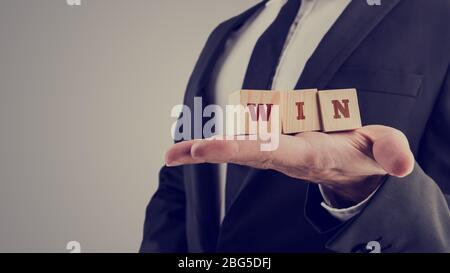 Imagen retro de hombre de negocios sosteniendo bloques de madera del alfabeto lectura - ganar - equilibrado en la palma de su mano con copyspace en una imagen conceptual.