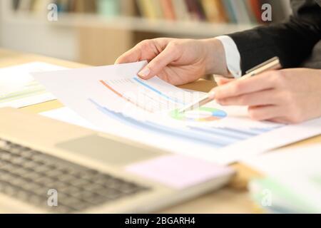Primer plano de la mujer emprendedora manos ckecking informe de crecimiento gráfico en un escritorio en la oficina doméstica