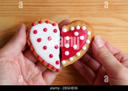 Mano del hombre y mano de la mujer sosteniendo dos galletas con forma de medio corazón se adhieren sobre fondo de madera