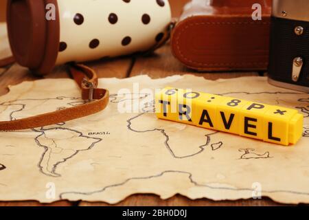Cámara retro en mapa del mundo con palabra Viajes sobre fondo de mesa de madera