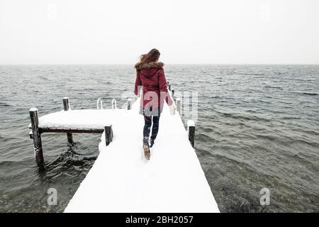 Vista posterior de una joven corriendo en un embarcadero cubierto de nieve en el Lago Starnberg, Alemania