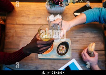 Dos personas sentadas en el restaurante, comer y beber, con tableta digital en la mesa
