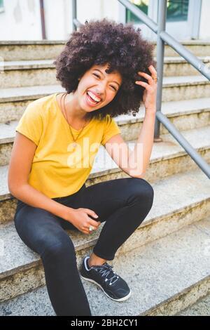 Retrato de una joven riendo sentada en las escaleras al aire libre