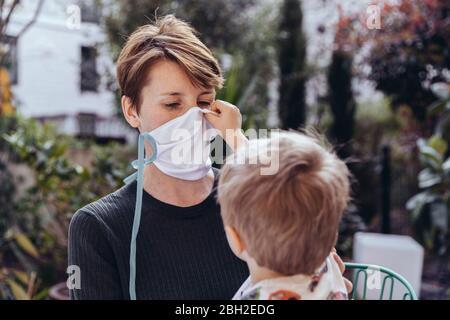 Littley niño ayudando a su madre a ponerse una máscara facial