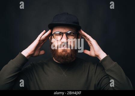 Concentrado. Me duele la cabeza. Estoy teniendo dolor de cabeza. Hombre con barba con los ojos cerrados tocando la cabeza sobre fondo negro. Foto de stock