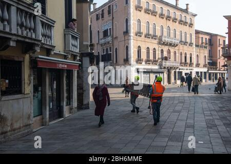 VENECIA, ITALIA - ABRIL 2020: La gente camina en calles casi vacías durante el cierre nacional para la pandemia de Covid-19.