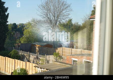 Contaminación urbana por humo de fuego de jardín. Los vecinos molestos estropean la tarde soleada durante el cierre del coronavirus británico! Dificultad respiratoria, asma.