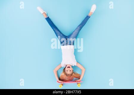 Arriba arriba vista en ángulo alto cuerpo entero foto de chica positiva deportiva niño paseo largo arriba abajo mostrar lengüeta fuera ropa blanca poner aislado encima