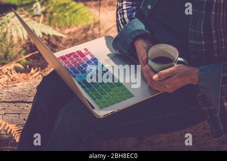 mujer cercana al aire libre con taza de café y un portátil en las piernas listo para trabajar y utilizar la conexión a internet - trabajando en todas partes sin límite de edad para la gente moderna y gratuita con ordenador y señal wifi