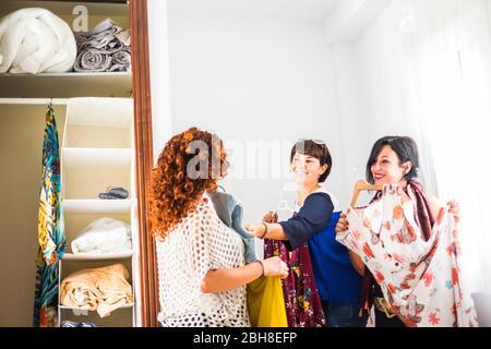 grupo de tres mujeres caucásicas jóvenes en casa eligiendo el vestido listo para los eventos nocturnos y celebrar juntos en amistad. sonrisas y buen ocio. colores y mucha ropa