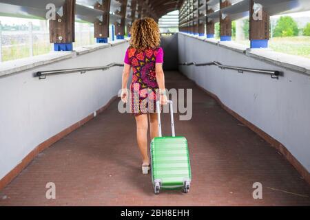 hermosa joven rubia cury mujer vista desde atrás viaje trasero y se mueven caminando con una bolsa de cabina verde carrito de equipaje. negro oscuro túnel frente a ella en el fondo